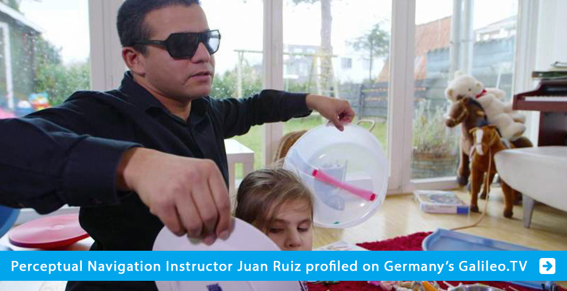 Banner slide shows Instructor Juan Ruiz holding plastic bowls to either side of a young girls's head inside a house. The logo for Galileo.tv is also superimposed. The text band reads: Perceptual Navigation Instructor Juan Ruiz profiled on Germany's Galileo.tv. Click on the banner to go to the story.