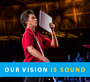 Column Box shows a photo of World Access For The Blind Founder and President Daniel Kish standing onstage at TED standing with a full-length navigation cane and making a 'shhhhh' sound against a flat panel he is holding up to demonstrate Flash Sonar Echolocation. The text banner reads: Our Vision Is Sound.