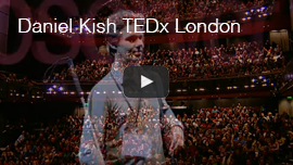 Video thumbnail shows a screen grab of Daniel Kish at the TEDX Observer event in London, England in 2012. The packed-house audience set on three levels is visible as a partial dissolve effect. Click here to go to the video on youtube.