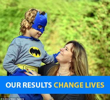Our Results Change Lives. Photo shows Jr. Visioneer Ruben dressed in a Batman costume and mask being held aloft by his Mum tridie as a tribute to the 'real-life Bat Man' Daniel Kish.