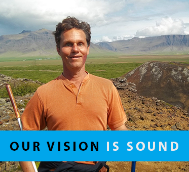Column Box shows a photo of World Access For The Blind Founder and President Daniel Kish hiking in a glacial field in Iceland with a full-length navigation cane and a hiking pole. The text banner reads: Our Vision Is Sound.