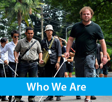 Who We Are. Photo shows WAFTB Perceptual Navigation Instructor Brian Bushway leading a group of blind students in Bangkok, Thailand.