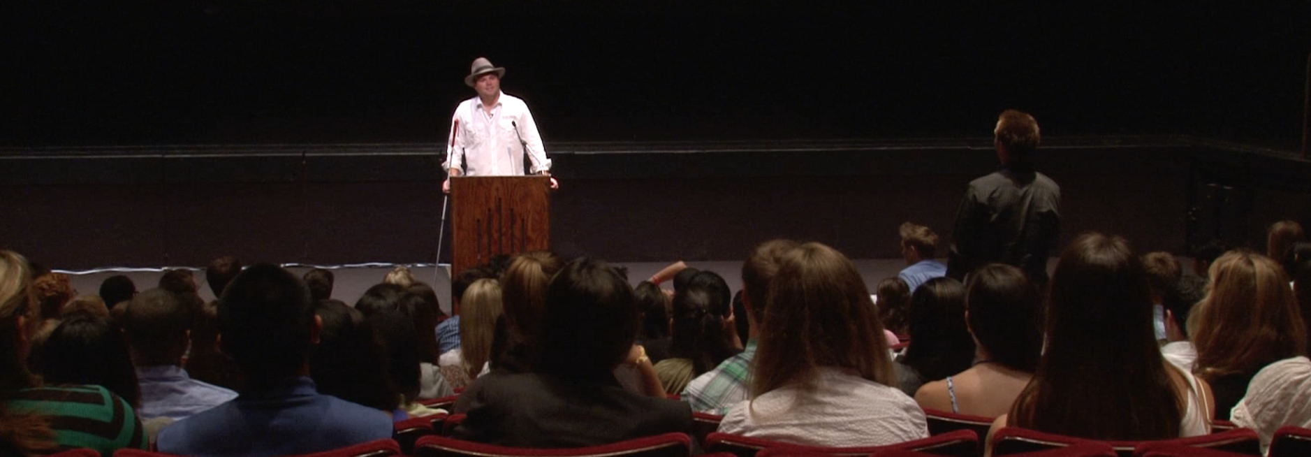 Photo shows Brian Bushway wearing a fedora hat while standing at a wooden lectern in a theater at Pepperdine University in Malibu, California as he speaks before former Heavyweight boxing champ George Foreman.
