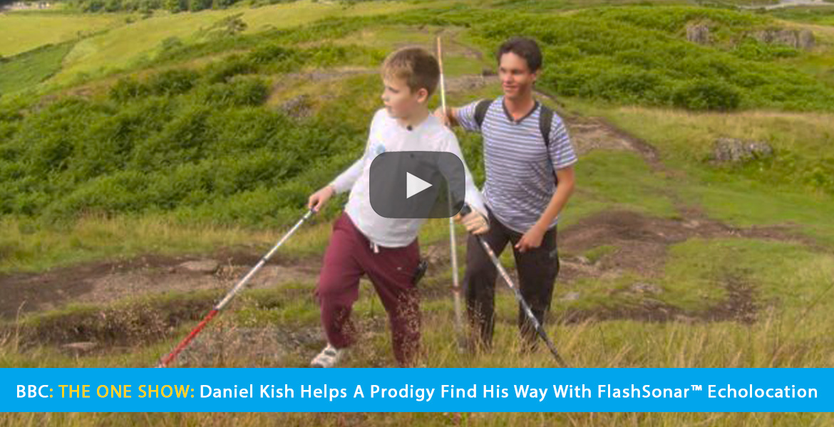 Large video thumbnail shows Daniel Kish walking up a green hill in Scotland behind Ethan Loch. The text banner reads: BBC: The One Show: Daniel Kish Helps A Prodigy Find His Way With Flash Sonar Echolocation. CLick on the banner to go to the video.