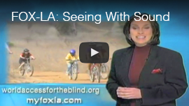 Video thumbnail from FOX L.A. shows anchor Christina Gonzalez standing in front of a video screen of Daniel Kish and other World Access For The Blind Perceptual Navigation Instructors and students cycling along a canyon trail. CLick on the thumbnail to go to the special report: 'Seeing with Sound'.