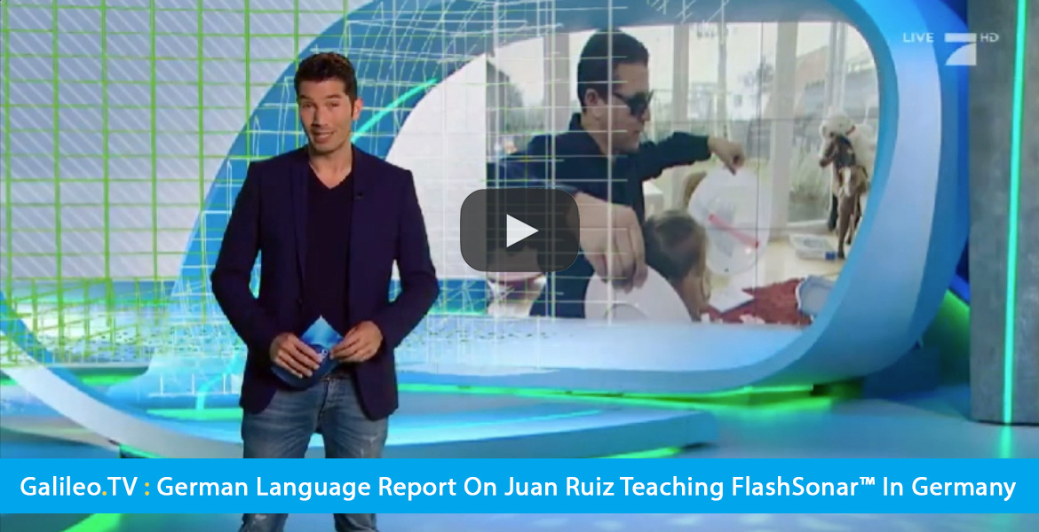 Large Video Thumbnail shows a host of the German-language Galileo TV standing on the studio set with a video wall in the background showing World Access For The Blind Perceptual Navigation Instructor Juan Ruiz working with a young girl. The text band reads: Galileo.TV: German Language Program reports on Juan Ruiz teaching FlashSonar™ in Germany. CLick the banner to go to the video.