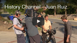 History Channel - Juan Ruiz video thumbnail shows World Access For The Blind Perceptual Navigation instructor Juan Ruiz setting up a shot with the camera crew as he sits on his mountain bike. Click on the thumbnail to go to the video.