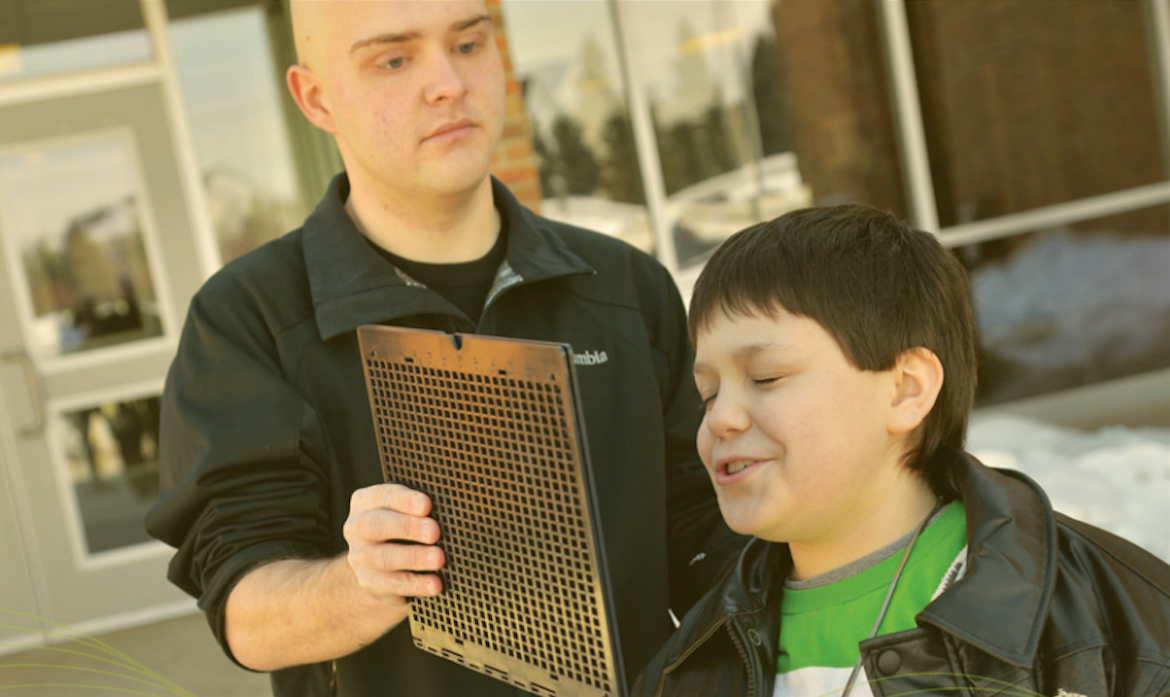 Photo: J Steele-Louchart holding up a mesh grate in front of blind student Anthony as he teaches him FlashSonar echolocation.