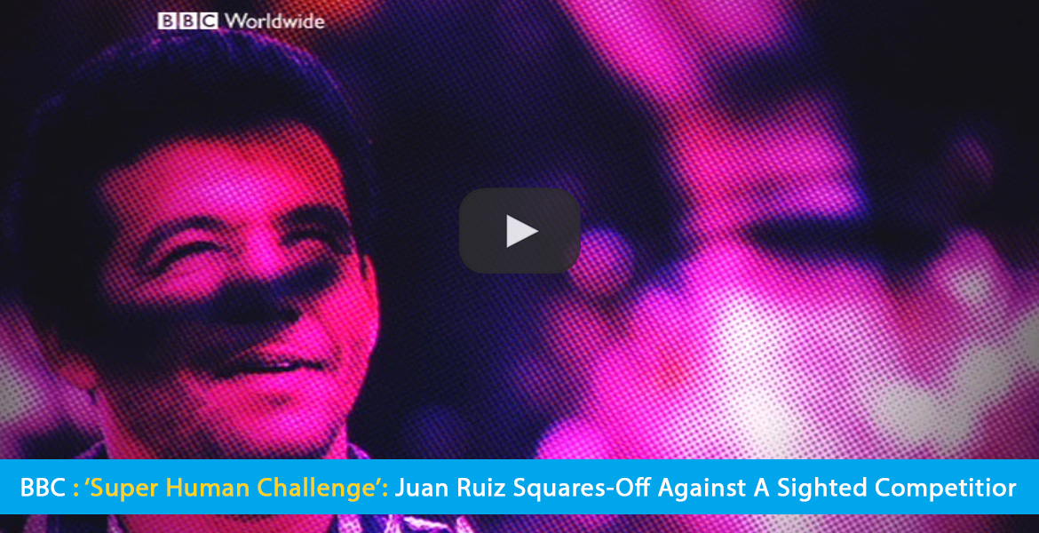 Large Video Thumbnail shows a graphic effect of two layered photos of World Access For The Blind Perceptual Navigation Instructor Juan Ruiz filtered with a deep pink and blue dot matrix effect. The text band reads: BBC: 'Super Human Challenge': Juan Ruiz squares-off against a sighted competitor. CLick on the thumbnail to go to the video.
