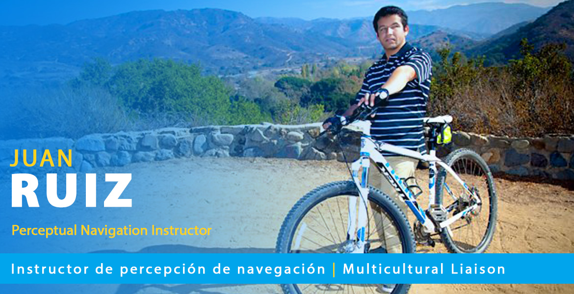 Page banner shows Juan Ruiz standing beside his mountain bike at a scenic mountain outlook point. Text overlay reads: Juan Ruiz: Perceptual Navigation Instructor. Text band reads Instructor de percepción de navegación | Multicultural Liaison.