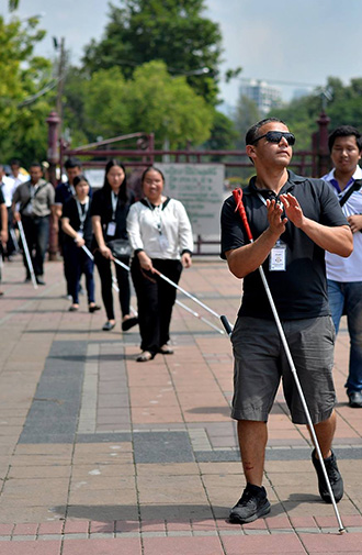 Photo: Juan Ruiz leads a group of blind coaching students through a square in Bangkok, Thailand. He is clapping his hands to determine the size of the open space.