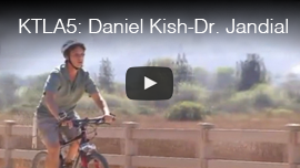 Video thumbnail from KTLA5 in Los Angeles shows World Access For the Blind President Daniel Kish cycling while wearing a helmet. Click on the thumbnail to go to the video.