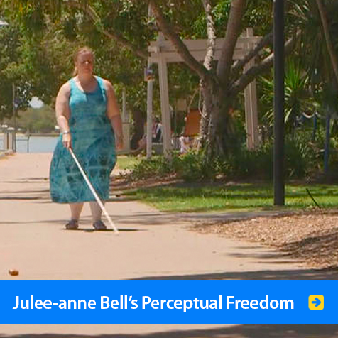 Julee-anne Bell's Perceptual Freedom. Image shows Julee-anne Bell walking in a park in Australia using FlashSonar Echolocation and a navigation cane.