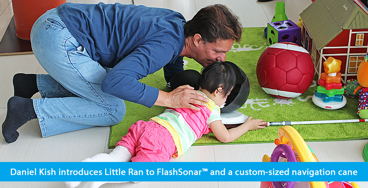 Daniel Kish introduces Little Ran to FlashSonar and a custom-sized navigation cane. Photo shows Daniel kneeling on a carpeted play area as Little Ran lies on her belly while Daniel positions a large plastic bowl by her face to introduce her to the concept of echoes.