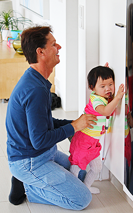 Image shows Daniel Kish kneeling behind and supporting Little Ran as she stands and leans against a cupboard door with her navigation cane leaning against her arm.