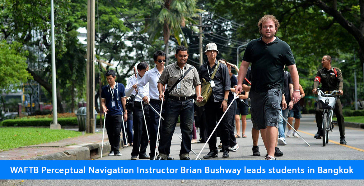 WAFTB Perceptual Navigation Instructor Brian Bushway leads students in Bangkok. Photo shows the group on a lush tree lined street with their full-length canes extended.