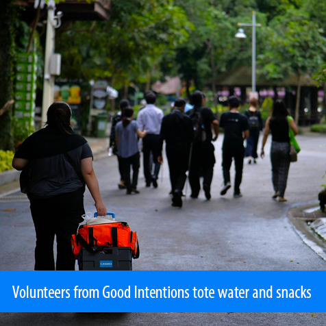 Volunteers from Good Intentions tote water and snacks. Image. A volunteer pulls a cart with water and snacks behind the group of students walking in the distance as they leave the zoo.