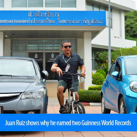 Juan Ruiz shows why he earned two Guinness World Records. Image shows Juan riding a bicycle between two cards on the parking lot of the Foundation for the Blinf in Thailand in Bangkok.