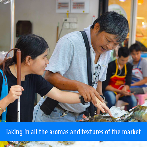 Taking in all the aromas and textures of the market. Image shows a volunteer guiding a female student's hand to some larges prawns at the fish market.