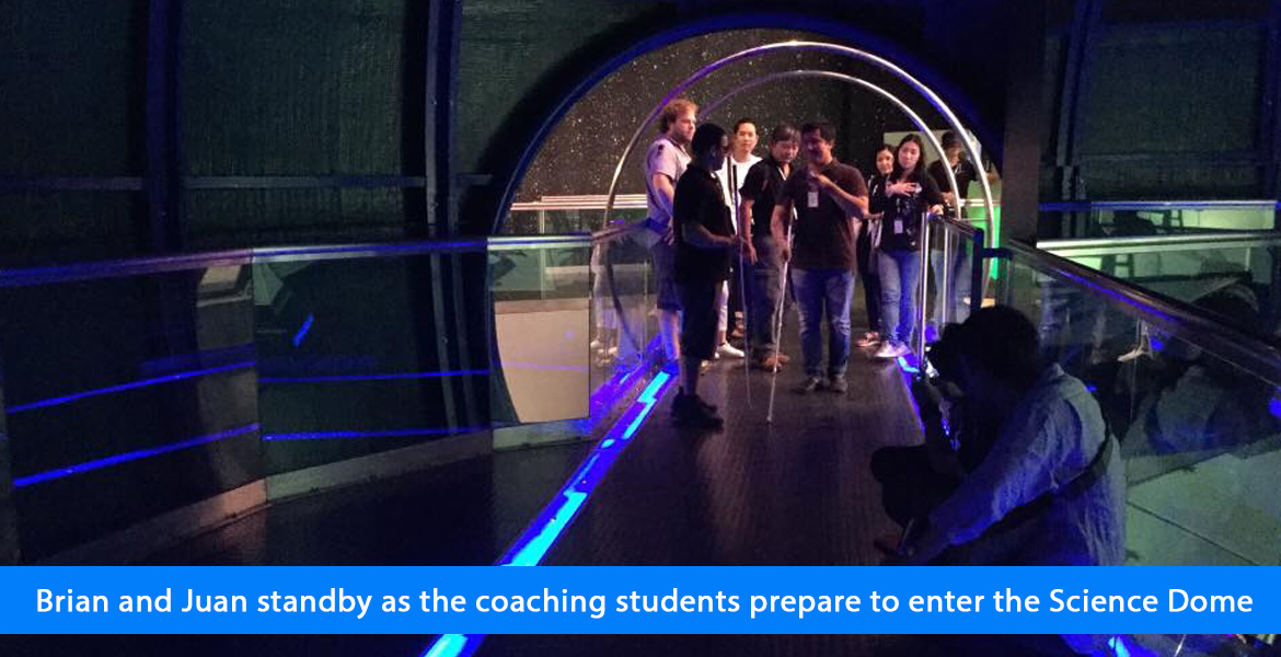 Juan and Brian standby as the coaching students prepare to enter the Science Dome. Image: Students stand by the circular entrance as they prepare to navigate a walkway flanked by blue lighting as they enter the Science Dome.