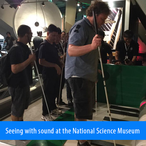 Seeing with sound at the National Science Museum. Image: Juan and the students stand nearby as Brian Bushway stands on a large piano keyboard floor like the one Tom Hanks stepped on in the movie 'Big'.
