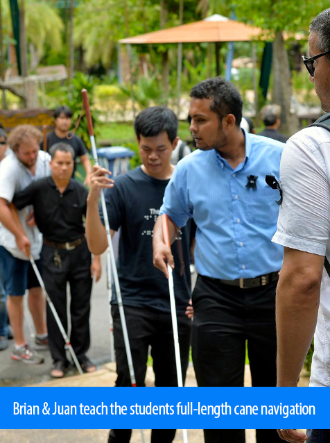 Juan and Brian teach the students full-length cane navigation. Image shows both Instructors working with a line of students on the grounds of a zoo in Bangkok.
