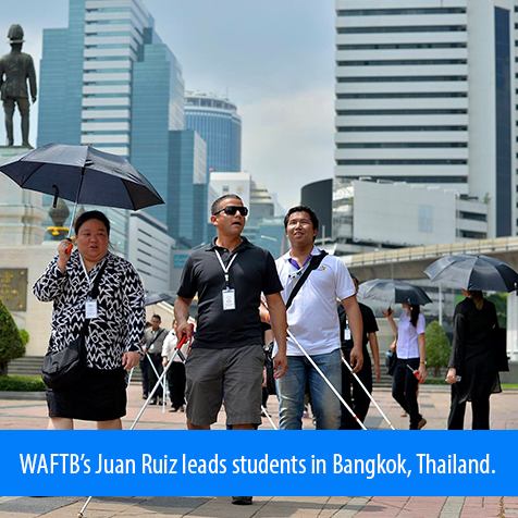 WAFTB's Juan Ruiz leads students in Bangkok, Thailand. Image shows a statue and hi-rise buildings in the background.