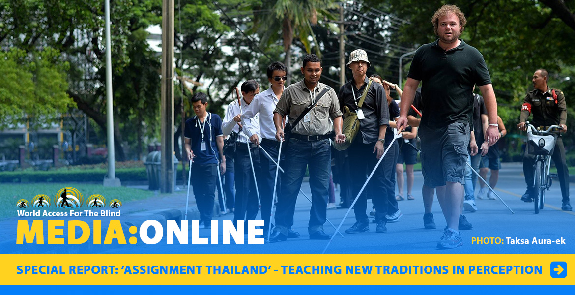 Media: Online: Assignment Thailand - Teaching New Traditions In Perception. Image: WAFTB Perceptual Navigation Instructor Brian Bushway leads a grooup of blind student navigation coaches on a street in Bangkok, Thailand.
