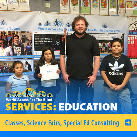 Services: Education: Classes, Science Fairs, Special Ed Consulting. Image: Photo shows WAFTB's Brian Bushway with three students at a school in the Los Angeles Area standing in front of a WAFTB Banner in their classroom.