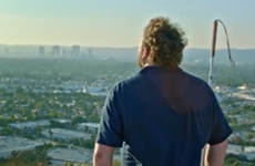 image: Video still from Uproxx profile of WAFTB Perceptual Navigation Instructor Brian Bushway, shows him standing at an look-out point in Culver City, California with the los Angeles skyline in front of him.