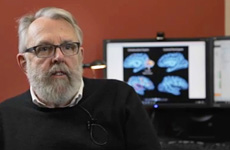 Video still of Professor Melvyn Goodale, Director of the Brain and Mind Institute at the University of Western Ontario, sitting in front of computer screens showing brain scans.