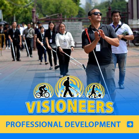Professional Development. Photo of Visioneer Juan Ruiz leading blind Visioneering coach trainees in a public square in Bangkok.