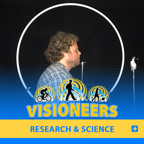 Research and Science. Image: Visioneer Brian Bushway stands in front of a microphone amd beside a large circular apparatus during a research partnership with Durham University in the UK.