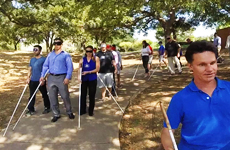 Image: Daniel Kish and Brian Bushway lead employees of Scottish American Insurance through the outdoor portion of a FlashSonar workshop. All the participants are wearing blindfolds.