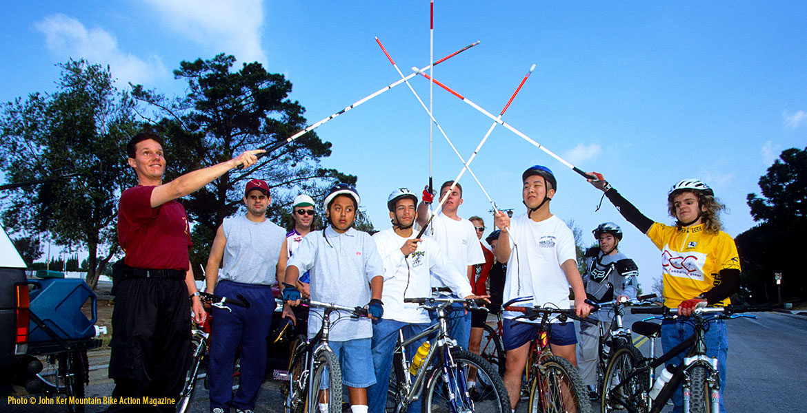 """Photo: Lead Visioneer Daniel Kish stands with blind students sitting on, or standing beside, their mountain bikes raising their canes in the air in an """"All for one, one for all"""" salute. Photo by John Ker for an article in the May 2001 edition of Mountain Bike Action Magazine."""