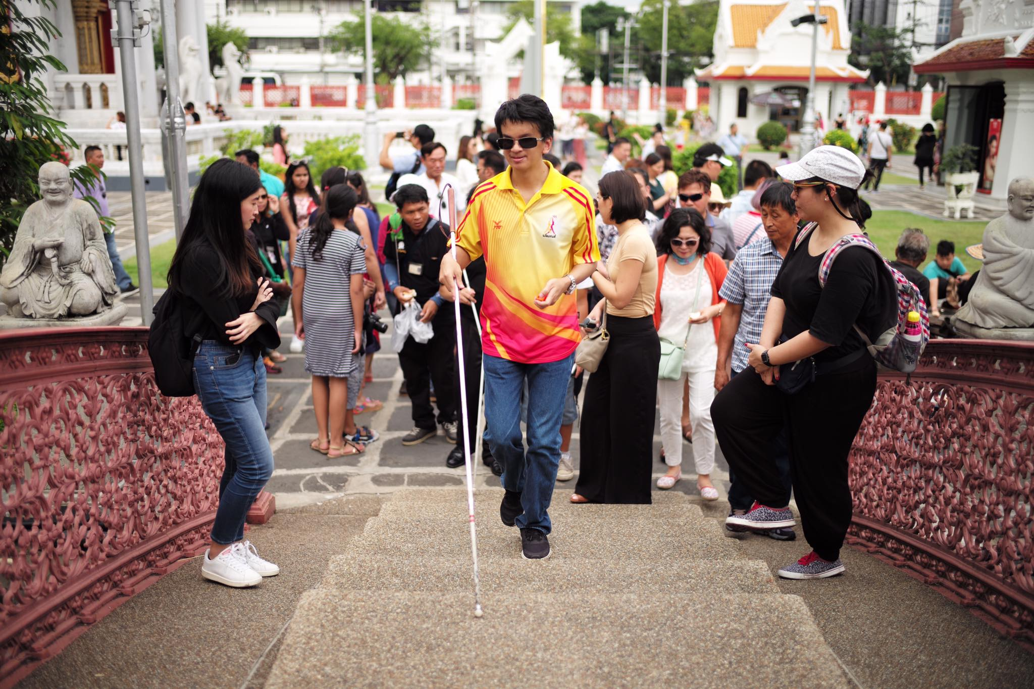 Blind Visioneer trainee coaches use FlashSonar echolocation and a long Perception Cane to navigate a temple in Bangkok, Thailand.