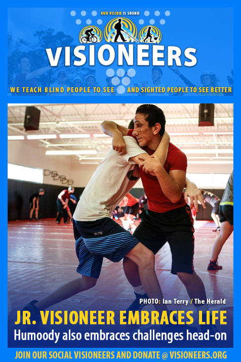Visioneers Facebook module frames a photo of Humoody Smith practicing wrestling moves with teammate Paul Johnson in his school's gym. Caption: Junior Visioneer Embraces Life. Humoody also embraces challenges head-on.