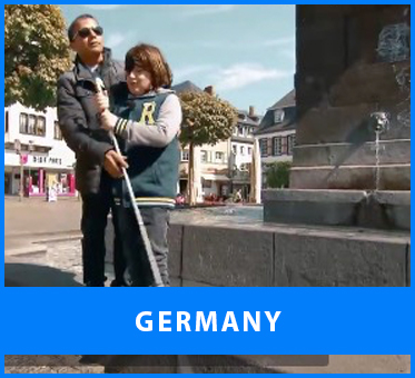 Germany. Image: Senior Multicultural Visioneer Juan Ruiz instructs a blind boy on how to use his long Perception Cane to detect the height of a step at an outdoor fountain in Germany.