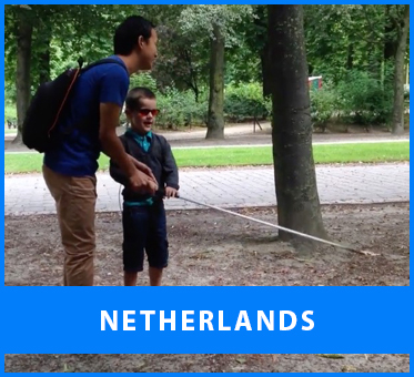 The Netherlands. Workshop Visoneer Thomas Tajo instructs a young blind boy on how to hold his long Perception Cane while navigating in a park,