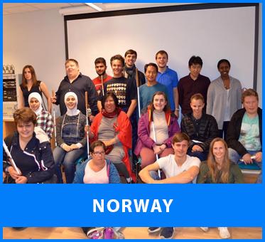 Norway. Image: Lead Visioneer Daniel Kish stands beside Workshop Visioneer Thomas Tajo in a group photo with blind students in Norway at a weekend workshop.