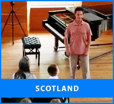 Scotland. Image: Lead Visioneer Daniel Kish speaks before a charity concert at the Lanark Community Hall by Junior Visioneer Ethan David Loch.